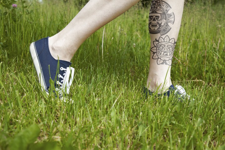 Walking on green grass in sport shoes