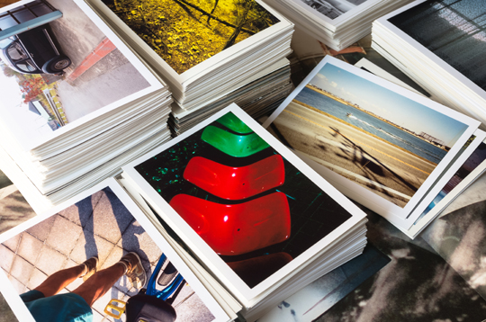 piles of photographs selected by Go Media